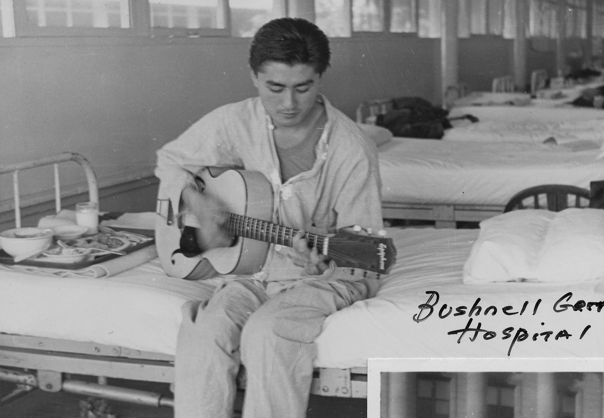 Bushnell patient Willie Higa playing the guitar