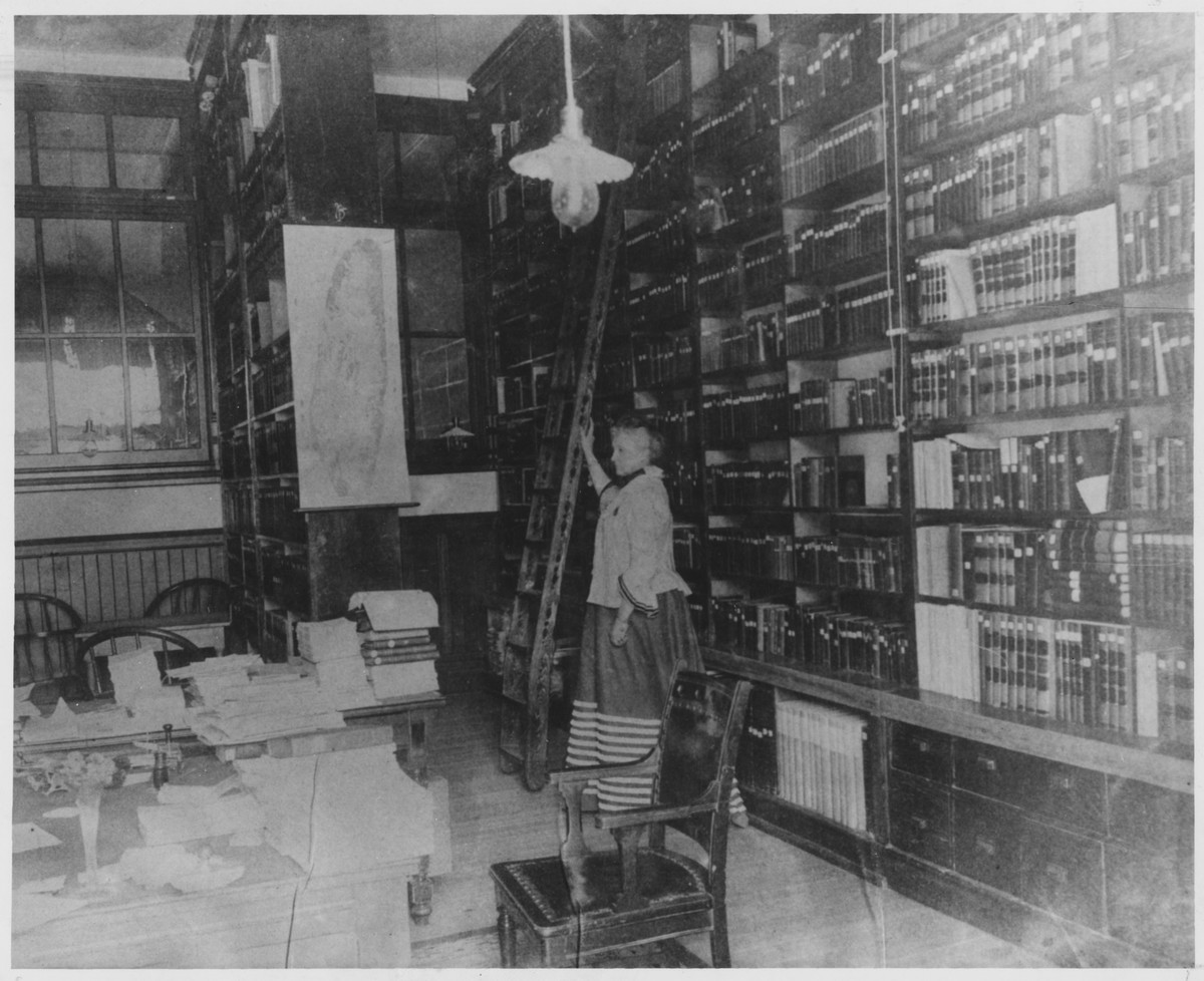 Sarah Godwin Brown Goodwin standing by the stack ladder in the library, 1903