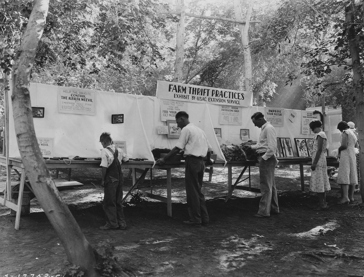 Men looking at the Farm Thrift Practice exhibit by the U.S.A.C Extension Service.;