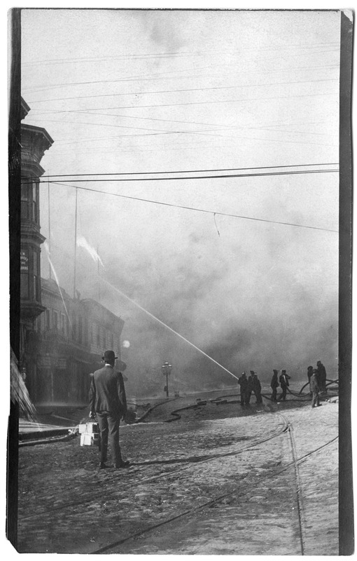 """Market and Elis looking east. Fireman at work, man taking boxes of cigars away."""