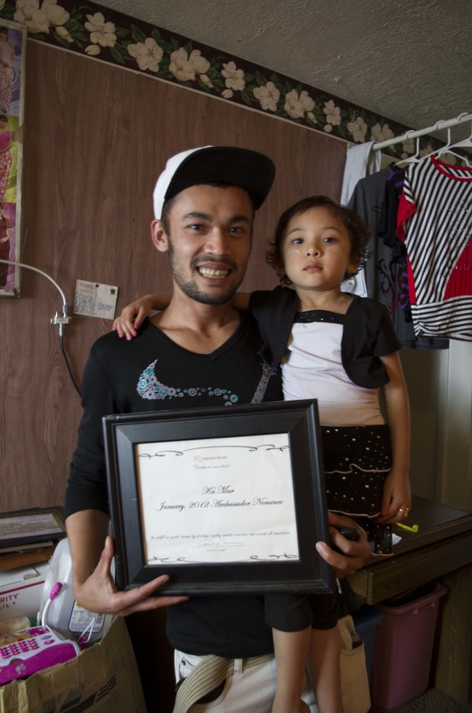 Ka Mar holds his daughter Ma Se Ma as he poses with one of several award certificates, Logan, Utah, May 15, 2015