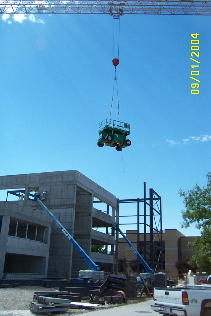 Crane moving heavy equipment during Merrill-Cazier Library construction<br />