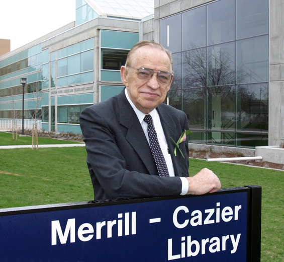 Image of Stan Cazier with the Merrill-Cazier LIbrary sign
