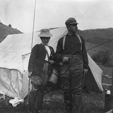 Man and woman holding fishing gear in front of tent