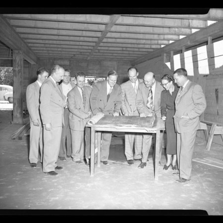 Individuals looking at the Student Union Building blueprints in the construction sight, c. 1951
