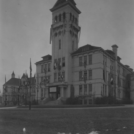 Old Main decorated with flags for the 145th Field Artillery return, January, 16, 1919