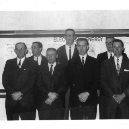 """Group of men standing in front of board entitled """"Electrical Energy"""""""