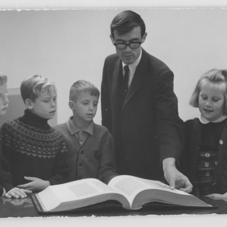 A.J. Simmonds showing a book to young children<br />