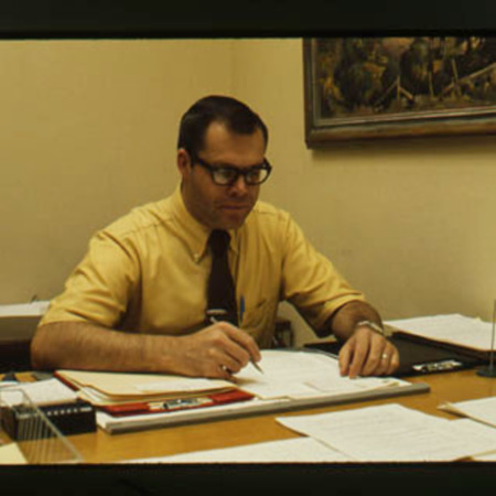 Russ Dean sitting at his desk<br />