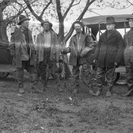 Group of six men standing in front of car, getting ready to fish