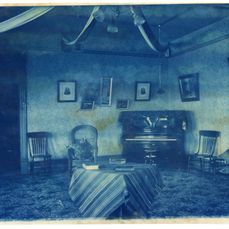 Dormitory reception room with a piano, a table with books and chairs, and portraits hanging on the wall (310)