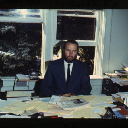 John Stewart sitting at his desk<br />