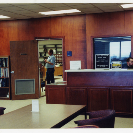 Dan Davis sitting at the Special Collections reading room desk, Merrill Library