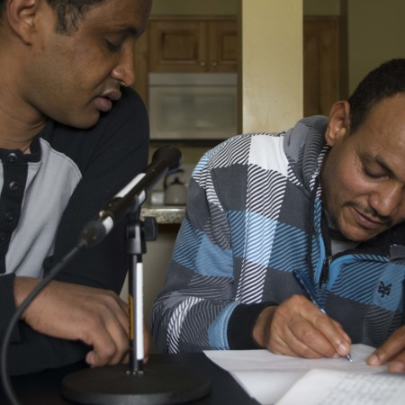 Afeworki Woldemichael signing the release form with Berhane Debesai Abraha, May 17, 2015
