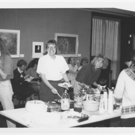 Mary Piette (seated left), Becky Olson (center at buffet), Melanie Shaw (far right at buffet) & others at a buffet in ML 102<br />