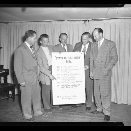 """A Group of men with a """"State of the Union Building"""" sign inside the Temporary Union Building, c. 1951"""
