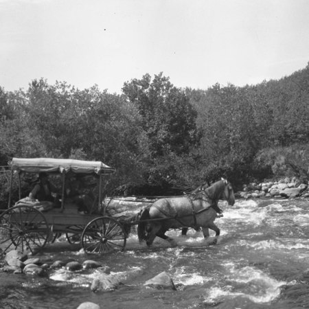 Team of horses pulling a carriage across river