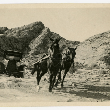 Two horses pulling the Maxwell across a hill