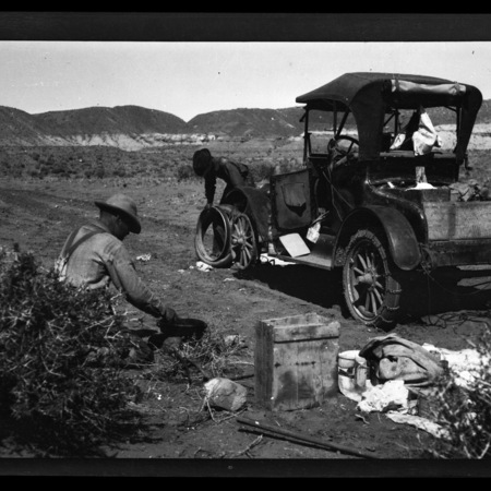 Two men fixing the tire of Dolph Andrus's Maxwell automobile, Monument Valley