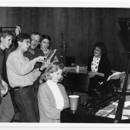 Left to right: Vic Cannon, Joel Hatch, Brad Cole, A.J. Simmonds, Noel Carmac, Ann Buttars & Lisa Hearne at the piano, Special Collections Christmas party in the Tanner Memorial Reading Room<br />