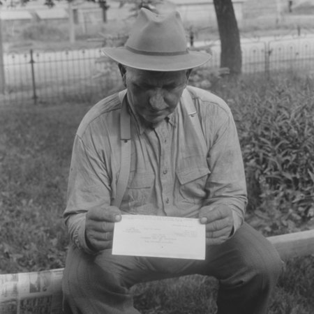 Wheat farmer reading a letter from the U.S.A.C. and the Utah Cooperative Extension Division dated 15 Aug. 1933;