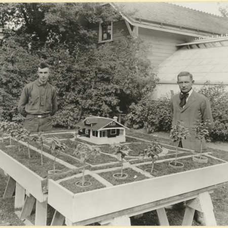 Emil Hansen and student next to a model house, 1920s