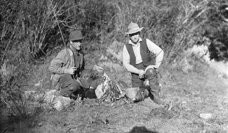 Two men with fishing rods and showing their catches