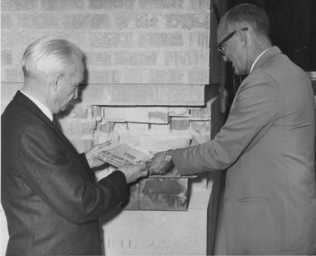 University President Daryl Chase and librarian Milton C. Abrams opening the cornerstone of the 1930 library building during the expansion of the Merrill Library, 1966