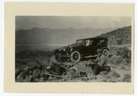 Shorty Harris and companion eating next to an automobile, Death Valley, 1920s