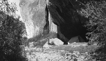 Man standing next to a tent set up under an overhanging rock