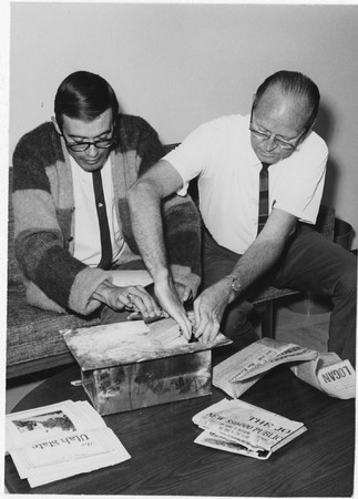 A. J. Simmonds and Burdette Peterson examine contents of 1930 library cornerstone, 1966