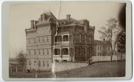 Photograph of the East Building that shows the Hezekiah Thatcher home in the background (21 October 1889)