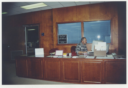 Archivist Robert Parson sitting at the Special Collections reading room desk, Merrill Library